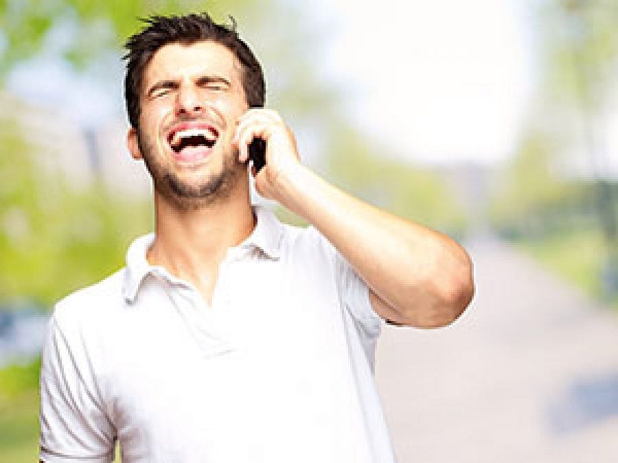 Man speaking by the phone and laughing